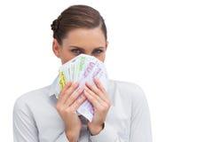 Femme d'affaires se cachant derrière l'argent dans des ses mains Image stock