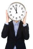 Femme d'affaires se cachant derrière la grande horloge Photos stock
