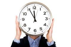 Femme d'affaires se cachant derrière la grande horloge Images stock