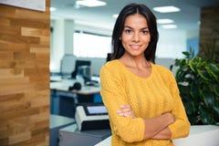 Femme d'affaires se tenant avec des bras pliés dans le bureau Images stock