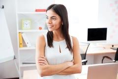 Femme d'affaires se tenant avec des bras pliés dans le bureau Image stock