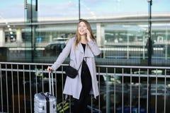 Femme d'affaires se tenant avec la mallette et parlant par smartpone près de l'aéroport Photo libre de droits