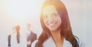 Femme d'affaires se tenant avec son personnel à l'arrière-plan au bureau Photo libre de droits