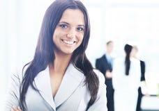Femme d'affaires se tenant avec son personnel à l'arrière-plan au bureau Image libre de droits