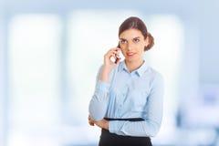 Femme d'affaires se tenant contre la fenêtre de bureau parlant au téléphone portable Image stock