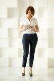 Femme d'affaires se tenant contre le mur blanc tout en regardant le comprimé Image libre de droits