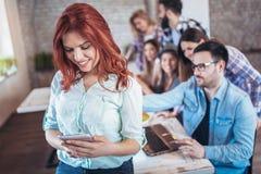 Femme d'affaires se tenant dans le bureau moderne et à l'aide du dispositif de comprimé photographie stock libre de droits