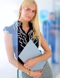 Femme d'affaires se tenant dans le premier plan avec un dossier dans des ses mains Image stock