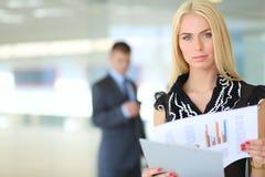 Femme d'affaires se tenant dans le premier plan avec un dossier dans des ses mains Photographie stock libre de droits