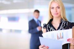 Femme d'affaires se tenant dans le premier plan avec un dossier dans des ses mains Photos stock