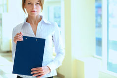 Femme d'affaires se tenant dans le premier plan avec un dossier dans des ses mains Images libres de droits