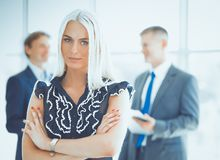 Femme d'affaires se tenant dans le premier plan avec un dossier dans des ses mains photo libre de droits