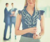 Femme d'affaires se tenant dans le premier plan avec un dossier dans des ses mains photographie stock