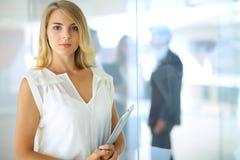 Femme d'affaires se tenant droite et smilling dans le bureau Images stock