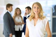 Femme d'affaires se tenant droite et smilling dans le bureau Image stock