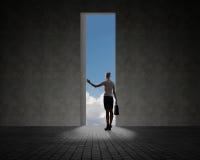 Femme d'affaires se tenant près d'un trou dans le mur Image libre de droits