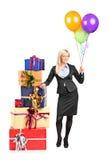 Femme d'affaires se tenant prêt une pile des présents Photos stock