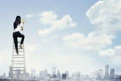 Femme d'affaires se tenant sur l'échelle haute et le cri avec le mégaphone Photo stock