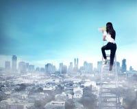 Femme d'affaires se tenant sur l'échelle haute et le cri avec le mégaphone Image stock