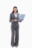 Femme d'affaires semblant heureuse avec un ordinateur portatif photo stock
