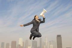 Femme d'affaires Shouting Into Megaphone au-dessus de ville Photographie stock