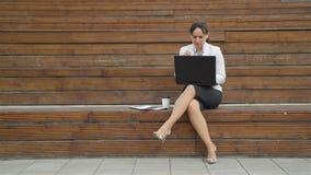 Femme d'affaires Sitting à un banc mangeant des nouilles banque de vidéos