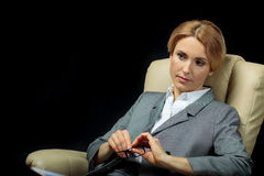 Femme d'affaires songeuse blonde dans le costume gris se reposant sur le fauteuil Photographie stock