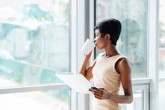 Femme d'affaires songeuse d'afro-américain avec du café potable de presse-papiers dans le bureau Photos stock