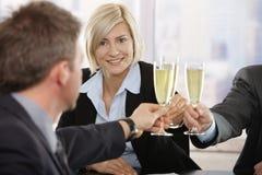 Femme d'affaires soulevant le pain grillé avec le champagne Image stock