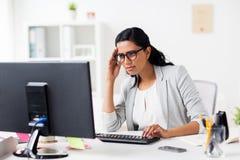Femme d'affaires soumise à une contrainte avec l'ordinateur au bureau Photographie stock libre de droits