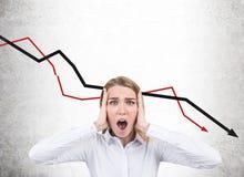 Femme d'affaires soumise à une contrainte et graphiques en baisse Photos stock