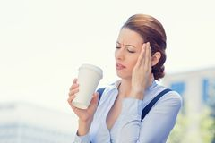 Femme d'affaires soumise à une contrainte par l'erreur ayant le mal de tête tenant le café de tasse images stock