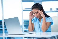 Femme d'affaires soumise à une contrainte travaillant à son bureau Image stock