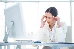 Femme d'affaires soumise à une contrainte travaillant à son bureau Photo stock
