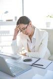 Femme d'affaires soumise à une contrainte travaillant à son bureau Photos stock