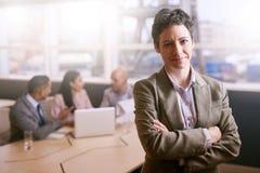 Femme d'affaires souriant à l'appareil-photo devant ses collègues Photographie stock libre de droits
