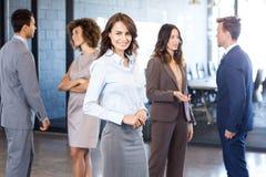 Femme d'affaires souriant à l'appareil-photo tandis que ses collègues discutant à l'arrière-plan Photographie stock