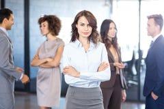 Femme d'affaires souriant à l'appareil-photo tandis que ses collègues discutant à l'arrière-plan Photographie stock libre de droits