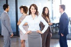 Femme d'affaires souriant à l'appareil-photo tandis que ses collègues discutant à l'arrière-plan Image libre de droits