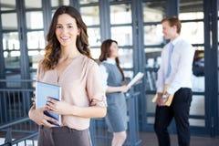 Femme d'affaires souriant à l'appareil-photo tandis que ses collègues discutant à l'arrière-plan Images libres de droits