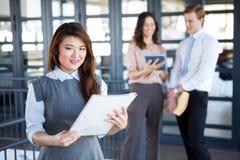Femme d'affaires souriant à l'appareil-photo tandis que ses collègues discutant à l'arrière-plan Photo stock