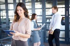 Femme d'affaires souriant à l'appareil-photo tandis que ses collègues discutant à l'arrière-plan Image stock
