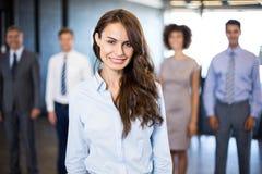 Femme d'affaires souriant à l'appareil-photo tandis que ses collègues se tenant à l'arrière-plan Image libre de droits