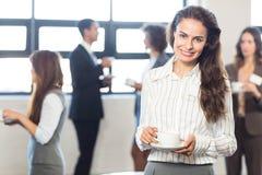 Femme d'affaires souriant à l'appareil-photo tandis que ses collègues se tenant à l'arrière-plan Photographie stock libre de droits