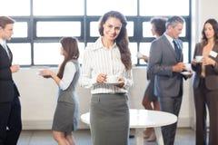 Femme d'affaires souriant à l'appareil-photo tandis que ses collègues se tenant à l'arrière-plan Photos libres de droits