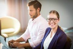 Femme d'affaires souriant à l'appareil-photo tandis que son collègue à l'aide de l'ordinateur portable Images libres de droits