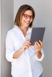 Femme d'affaires souriant avec le comprimé numérique Photos stock
