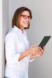Femme d'affaires souriant et tenant le comprimé numérique Photos stock