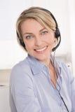 Femme d'affaires supérieure blonde attirante avec l'écouteur. Photos stock