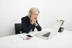 Femme d'affaires supérieure choquée à l'aide de l'ordinateur portable au bureau dans le bureau Image libre de droits